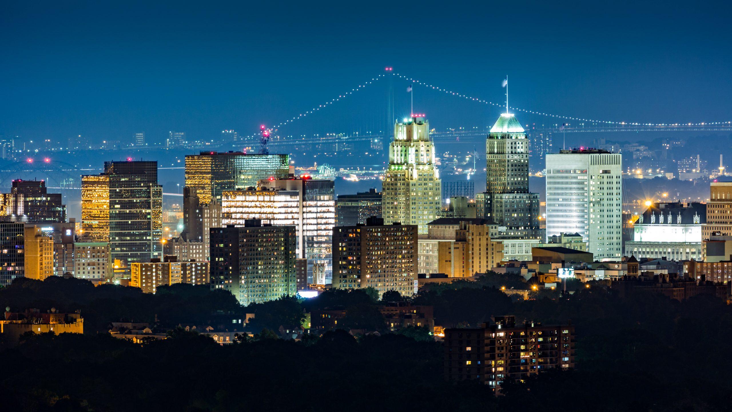 Newark, NJ, skyline on a hazy night with Verrazano Narrows bridge in the background.